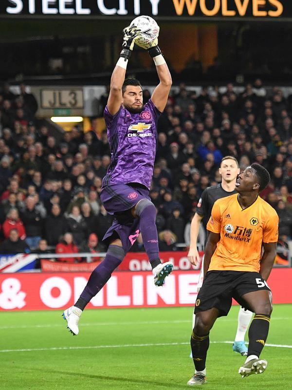 Kiper Manchester United, Sergio Romero menangkap bola atas serangan pemain Wolverhampton Wanderers pada babak ketiga Piala FA di Molineux, Sabtu (4/1/2020). Wolverhampton dan MU dipaksa untuk melakukan laga ulangan di Old Trafford usai bermain imbang tanpa gol. (Justin TALLIS/AFP)