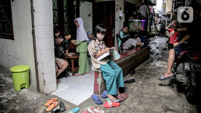 Seorang murid SD mengikuti kegiatan pembelajaran jarak jauh di depan rumahnya di RT 003 RW 006 Bendungan Hilir, Tanah Abang, Jakarta, Jumat (14/8/2020). Selama Covid-19, anak-anak memanfaatkan televisi yang ada untuk mengikuti pelajaran sekolah yang disiarkan TVRI. (Liputan6.com/Faizal Fanani)