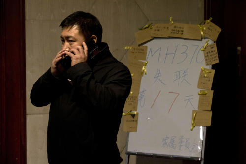 """A man whispers on a cellphone near a board which reads """"MH370 missing day 17"""" at a room reserved for relatives of Chinese passengers aboard the missing Malaysia Airlines jet in Beijing, China, Monday, March 24, 2014. Rain was expected to hamper the hunt Monday for debris suspected of being from the missing Malaysia Airlines jet, as the United States prepared to move a specialized device that can locate black boxes into the south Indian Ocean region. (AP Photo/Ng Han Guan)"""