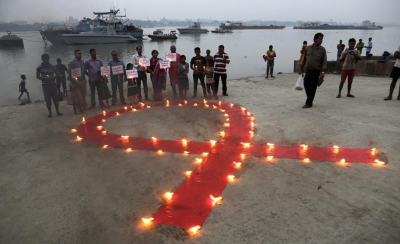 Volunteers stand with placards beside a huge red ribbon lighted with lamps during an awareness rally on AIDS day on the banks of the Ganges River in Kolkata, India, Tuesday, Dec. 1, 2015. (AP Photo/ Bikas Das)