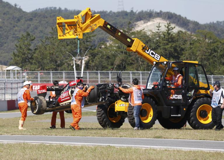 Workers remove the car of Lotus Formula One driver Raikkonen after it crashed during the first practice session of the Korean F1 Grand Prix in Yeongam