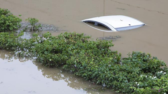Sebuah mobil terendam di underpass jalan yang banjir menyusul hujan monsun di Gurgaon di pinggiran New Delhi (19/8/2020). Hujan lebat melanda New Delhi pada 19 Agustus, membanjiri jalan dan menumpuk kesengsaraan bagi penumpang di ibu kota India yang kacau balau. (AFP/Xavier Galiana)
