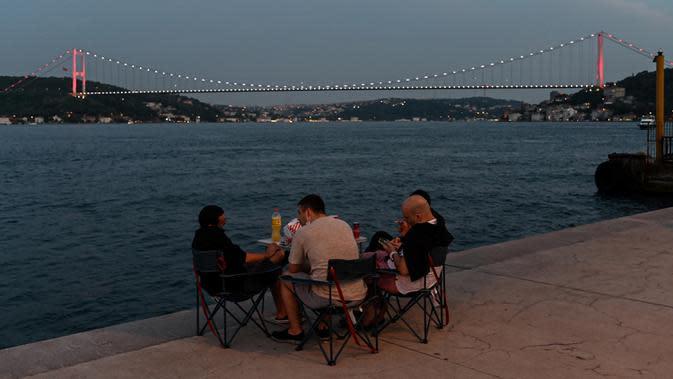 Orang-orang menikmati malam di sebelah pantai Bosphorus ketika jembatan Fatih Sultan Mehmet terlihat di Istanbul (6/7/2020). Jembatan Fatih Sultan Mehmet, yang dikenal dengan sebutan Jembatan Bosporus Kedua, adalah sebuah jembatan di Istanbul, Turki yang melintasi selat Bosporus. (AFP/Ozan Kose)