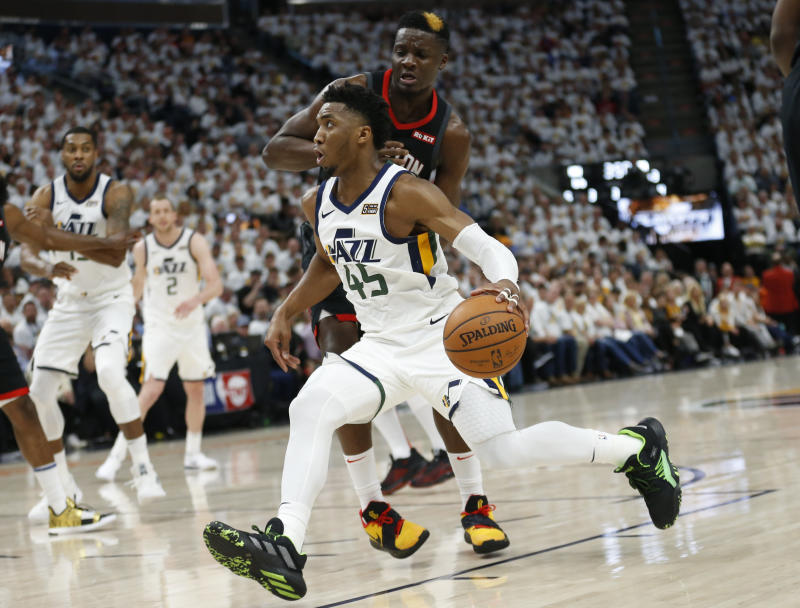 Utah Jazz guard Donovan Mitchell (45) drives around Houston Rockets center Clint Capela, rear, in the second half during Game 4 of a first-round NBA basketball playoff series Monday, April 22, 2019, in Salt Lake City. (AP Photo/Rick Bowmer)