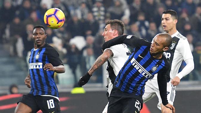 Striker Juventus, Mario Mandzukic, memperebutkan bola dengan bek tengah Inter Milan, Joao Miranda, dalam laga lanjutan Serie A di Allianz Stadium, Sabtu (8/12/2018) dini hari WIB. (Alessandro Di Marco/ANSA via AP)