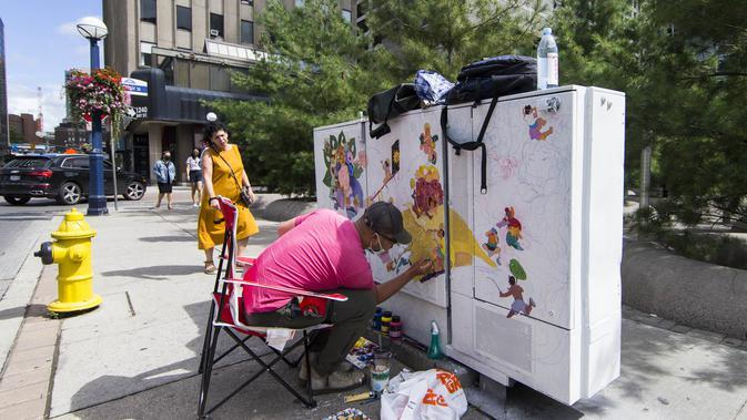 Seniman mengerjakan muralnya dalam acara Yorkville Murals 2020 di Toronto, Kanada (29/8/2020). Dengan karya mural artistik dan implementasi aktivasi budaya, acara tahunan ini dimulai Jumat (28/8) hingga Minggu (30/8) sebagai perayaan seni publik dan gerakan mural kontemporer. (Xinhua/Zou Zheng)