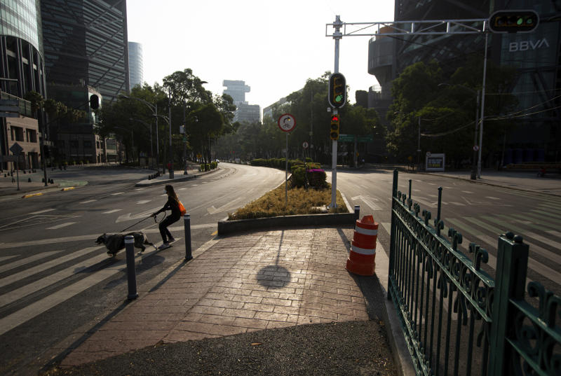 A young woman wearing a protective face mask controls her dog at a crossing of an empty Paseo de la Reforma in Mexico City, Sunday, April 26, 2020. (AP Photo/Fernando Llano)