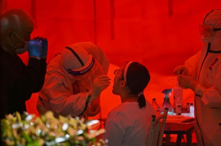 A medical worker takes a swab sample from a woman to be tested for the COVID-19 coronavirus in Wuhan, China's central Hubei province