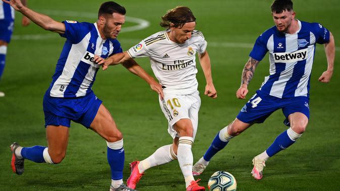 Gelandang Real Madrid, Luka Modric, berebut bola dengan penyerang Alaves, Lucas Perez, pada laga lanjutan La Liga pekan ke-35 di Stadion Alfredo di Stefano, Sabtu (11/7/2020) dini hari WIB. Real Madrid menang 2-0 atas Alaves. (AFP/Gabriel Bouys)
