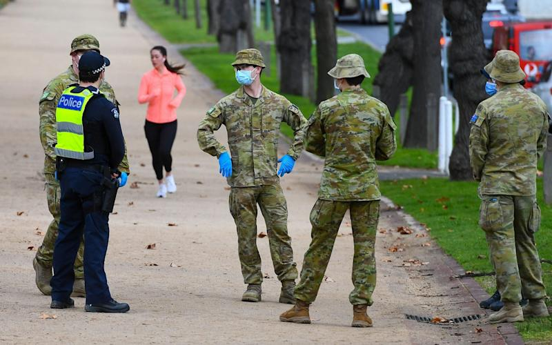 Police officers and soldiers patrol a popular running track in Melbourne to enforce new restrictive virus-control measures - WILLIAM WEST/AFP