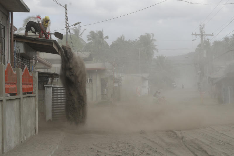 Residents shovel volcanic ash from the roof of their homes at a village near Taal volcano where people have evacuated to safer grounds in Agoncillo, Batangas province, southern Philippines on Saturday Jan. 18, 2020. Local authorities have allowed some residents to return to their homes for a few hours in the morning to retrieve belongings and feed their pets or farm animals. The Taal volcano near the Philippine capital emitted more ash clouds Saturday, posing the threat of another eruption. (AP Photo/Aaron Favila)