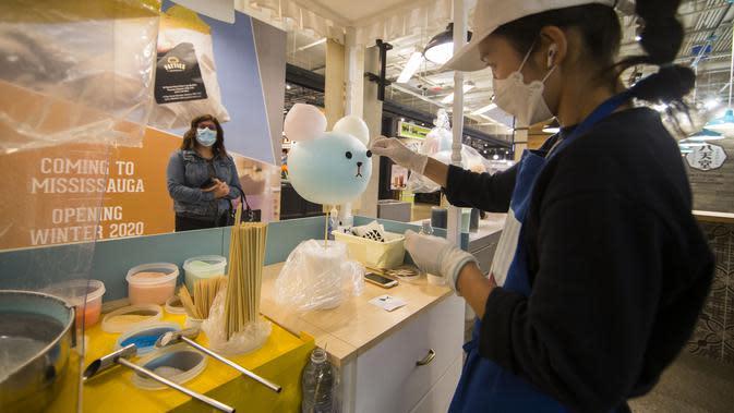 Seorang penjual yang mengenakan masker membuat permen kapas di Square One Shopping Center di Mississauga, Ontario, Kanada (9/10/2020). Negara itu menambah 378.000 lapangan kerja pada September, meningkat 2,1 persen, jauh melebihi ekspektasi. (Xinhua/Zou Zheng)