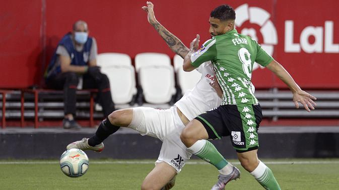 Gelandang Sevilla, Lucas Ocampos, berebut bola dengan gelandang Real Betis, Nabil Fekir, pada laga lanjutan La Liga di Estadio Ramon Sanchez Pizjuan, Jumat (12/6/2020) dini hari WIB. Sevilla menang 2-0 atas Real Betis. (AFP/Cristina Quicler)