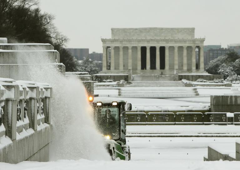 National Park Service tractor plows snow near World War II and Lincoln Memorials in Washington
