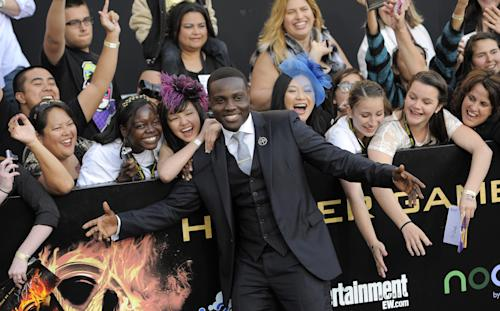 """Actor Dayo Okeniyi poses with fans as he arrives at the world premiere of """"The Hunger Games"""" on Monday March 12, 2012 in Los Angeles. (AP Photo/Chris Pizzello)"""