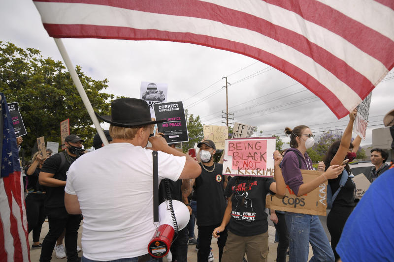 Demonstrators argue with Bruce Boyer, left, who was using a megaphone to ask protesters questions about why they were there during the protest, Saturday, June 6, 2020, in Simi Valley, Calif., over the death of George Floyd. Floyd died after he was restrained in police custody on Memorial Day in Minneapolis. (AP Photo/Mark J. Terrill)
