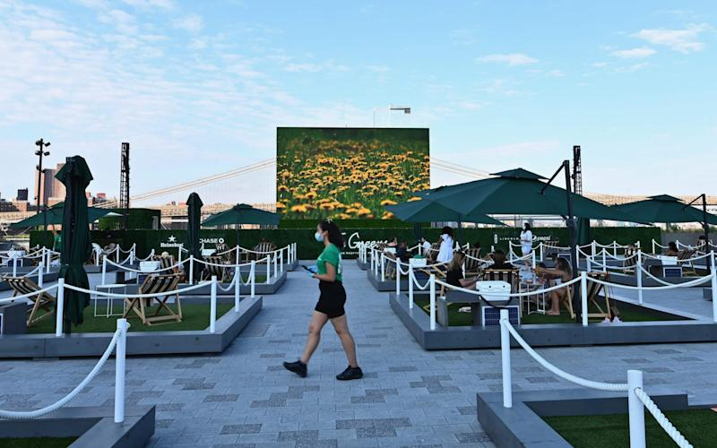 """People relax on socially distant mini lawns at the rooftop of Pier 17, called """"The Greens"""", in New York. The venue had to cancel its entire run of concerts and special events this season due to the Covid-19 - ANGELA WEISS/AFP"""