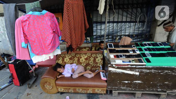 Seorang anak tidur di samping pedagang barang bekas di Kebayoran Vintage, Jakarta, Rabu (30/9/2020). Selama masa pandemi penjualan barang-barang bekas rumah tangga di meningkat hingga 75 %. (merdeka.com/Arie Basuki)