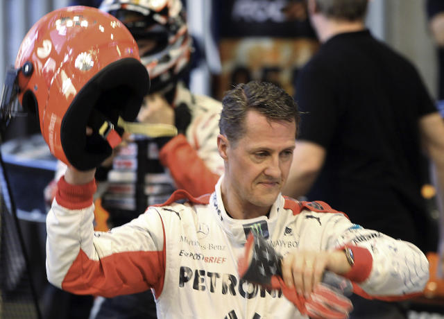 FILE - This is a Sunday, Dec. 16, 2012. file photo of Michael Schumacher of Germany as he holds a helmet after a test drive prior to the Race Of Champions at Rajamangala national stadium in Bangkok, Thailand. Doctors in Grenoble France treating former seven-time World Formula One champion Michael Schumacher refused Monday Dec. 30, 2013 to predict the outcome for the former Formula One driver, saying they were taking his very critical head injury