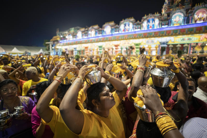 In this Feb. 8, 2020, photo, Hindu devotees carry milk pots on their heads in a procession during the Thaipusam festival at Batu Caves, in Selangor, Malaysia. Tens of thousands of ethnic Hindus, meanwhile, gathered last weekend to celebrate the annual festival, undeterred by the outbreak of a new virus. (AP Photo/Vincent Thian)
