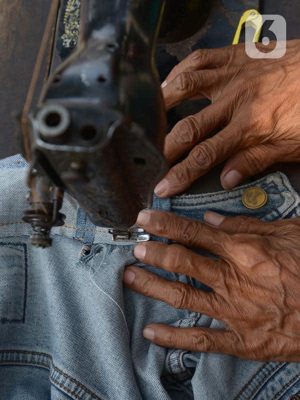 Sutayono menyelesaikan jahitan pelanggan di kawasan Matraman, Jakarta, Jumat (24/7/2020). Pria 74 tahun yang rencananya berangkat menunaikan ibadah haji pada 2022 mendatang, harus menunggu lagi hingga 2024 akibat keberangkatannya diundur karena pandemi Covid-19. (merdeka.com Imam Buhori)