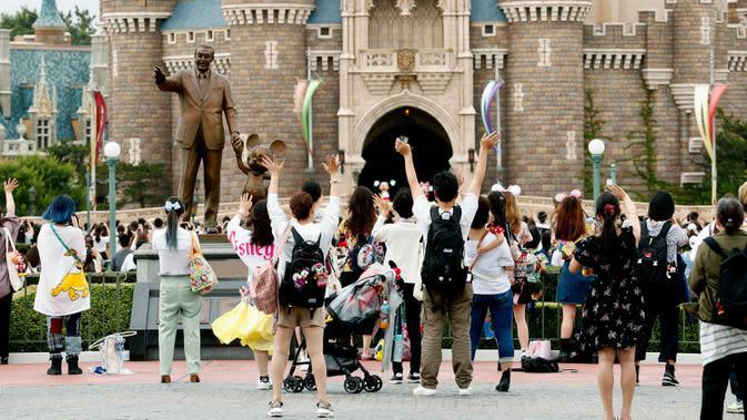 Pengunjung melambai tangan kepada karakter Disney yang tampil di Tokyo Disneyland di Urayasu, dekat Tokyo, Rabu (1/7/2020). Tokyo Disneyland dibuka kembali untuk pertama kalinya dalam empat bulan setelah sempat ditutup karena penyebaran Covid-19 . (Kyodo News via AP)
