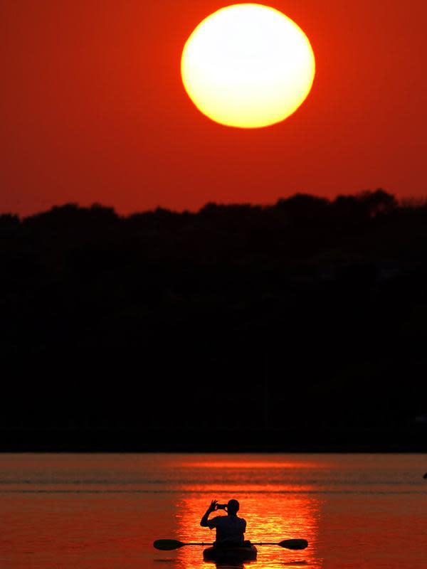 Seorang pria memotret matahari terbenam saat berperahu di Shawnee Mission Lake, Shawnee, Kansas, Amerika Serikat, Jumat (9/10/2020). Matahari terbenam terus lebih cerah dari biasanya karena asap dari kebakaran hutan barat terus melayang di seluruh negeri. (AP Photo/Charlie Riedel)