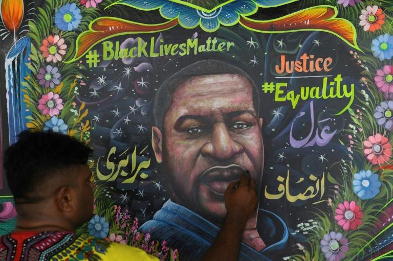 A Pakistani artist puts the final touches on a mural of George Floyd, the African American whose killing by a white police officer has ignited protests against racism around the world