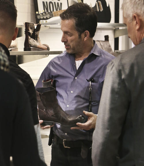 This Jan. 29, 2013 photo shows designer Kenneth Cole, second from left, with his shoe design team in New York. Cole returns to New York Fashion Week Thursday, Feb. 6, after a seven-year hiatus, seemingly putting his hand on everything before the runway lights go up: the clothes, the shoes, the handbags, the hashtags. He bought his company back from investors last year, and it's once again privately owned with Cole fully in charge. (AP Photo/Bebeto Matthews)