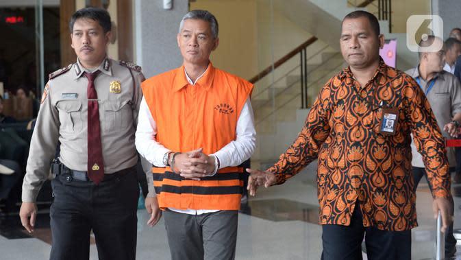 Komisioner KPU Wahyu Setiawan (rompi tahanan) dikawal petugas seusai menjalani pemeriksaan di gedung KPK, Jakarta, Rabu (15/1/2020). Wahyu Setiawan diperiksa perdana setelah ditetapkan sebagai tersangka terkait dugaan penerimaan suap penetapan anggota DPR terplih 2019-2020. (merdeka.com/Dwi Narwoko)