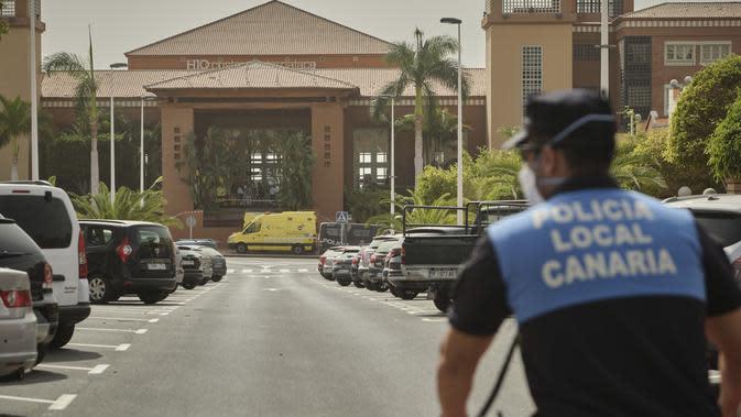 Seorang petugas polisi berdiri di depan hotel H10 Costa Adeje Palace di mana sebuah ambulans diparkir di Tenerife, Canary Island, Spanyol, Selasa, (25/2/2020). Hotel ini diisolasi setelah salah satu kliennya, turis Italia, dinyatakan positif mengalami kontraksi dengan virus corona. (AP Photo)