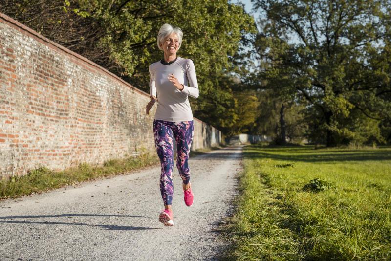 Senior woman running along brick wall in a park