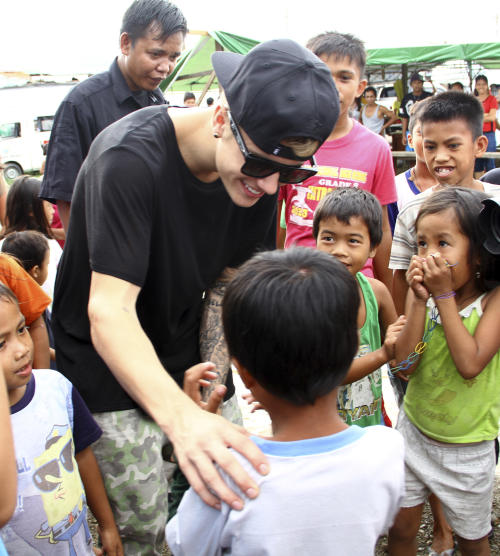 Justin Bieber greets children-survivors of Typhoon Haiyan during his visit to Tacloban city, Leyte province in central Philippines, Tuesday, Dec. 10, 2013. The teen heartthrob Bieber arrived Tuesday in the Philippines, where he has launched a campaign to help victims of last month's killer typhoon. (AP Photo)
