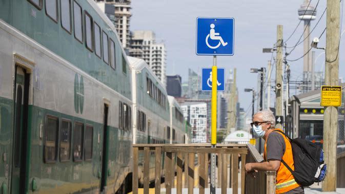 Seorang pria yang mengenakan masker terlihat di peron stasiun kereta Go di Toronto, Kanada (21/7/2020). Mulai Selasa (21/7), para pelanggan layanan transportasi umum di Kanada, Go Transit, diwajibkan mengenakan masker atau penutup wajah. (Xinhua/Zou Zheng)