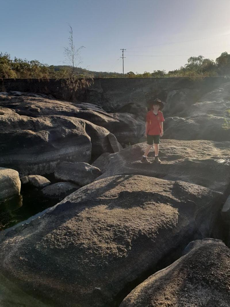 A young boy stands on a rock that forms part of a riverbed.