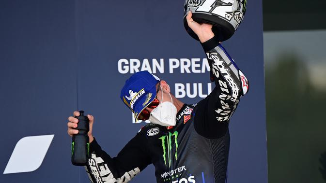 Maverick Vinales tetap gunakan masker ketika naik podium kedua MotoGP Jerez. (JAVIER SORIANO / AFP)