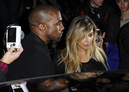 FILE - In this Sept. 29, 2013 file photo, Kanye West, left, and Kim Kardashian leave after attending Givenchy's ready-to-wear Spring/Summer 2014 fashion collection in Paris. (AP Photo/Zacharie Scheurer, File)