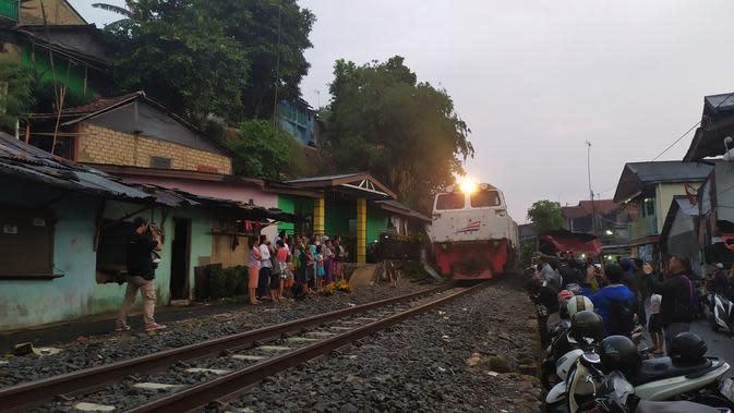 Kereta api tengah melintas di kawasan penduduk di daerah Bogor. (Liputan6.com/Achmad Sudarno)