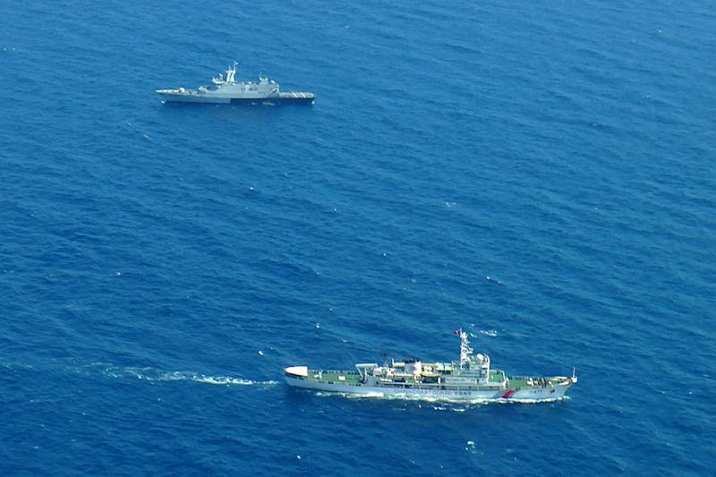 A Chinese coast guard (bottom) and a Malaysian navy ship patrolling the waters during search and rescue operations for the missing MH370 in the waters off the northeastern coast of the peninsula. – Pic courtesy of Malaysian Maritime Enforcement Agency, March 11, 2014.
