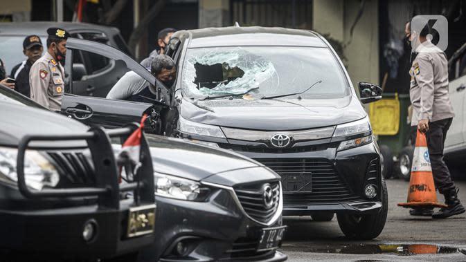 Petugas kepolisian mengecek salah satu mobil yang rusak pascapenyerangan di Polsek Ciracas, Jakarta, Sabtu (29/8/2020). Polsek Ciracas diserang oleh sejumlah orang tak dikenal pada Sabtu (29/8) dini hari. (Liputan6.com/Faizal Fanani)
