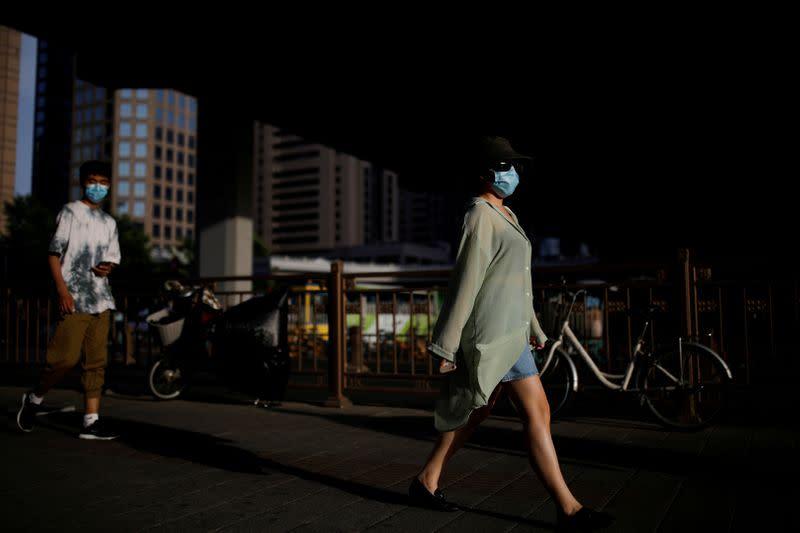 FILE PHOTO: People wearing face masks following the coronavirus disease (COVID-19) outbreak walk under an overpass in Beijing
