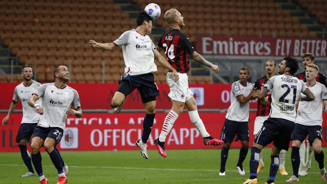 Pemain AC Milan Simon Kjaer (kanan) berebut bola udara dengan pemain Bologna Takehiro Tomiyasu pada pertandingan Serie A di Stadion San Siro, Milan, Italia, Senin (21/9/2020). AC Milan menaklukkan Bologna 2-0. (AP Photo/Antonio Calanni)