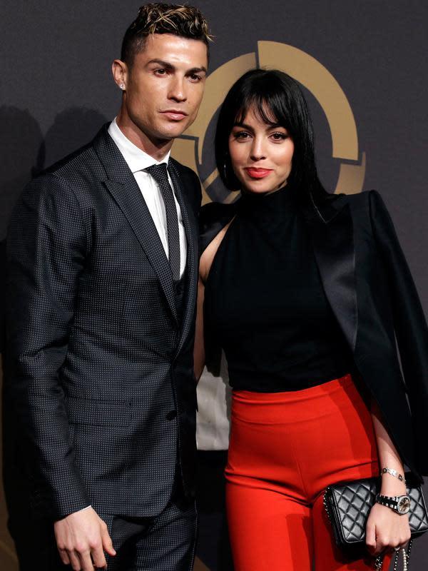 Bintang Real Madrid, Cristiano Ronaldo ditemani kekasihnya, Georgina Rodriguez menghadiri acara Quina Awards di Lisbon, Portugal, Senin (19/3). Tubuh Georgina tampak sudah kembali seperti semula setelah melahirkan pada November 2017. (AP/Armando Franca)
