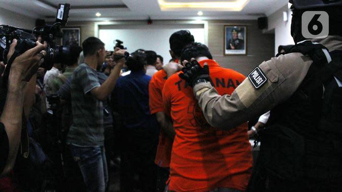 Polisi menggiring pelaku kasus prostitusi online di Apartemen Kalibata City saat konferensi pers di Polres Metro Jakarta Selatan, Rabu (29/1/2020). Polisi masih mendalami siapa saja pelanggan prostitusi online tersebut. (merdeka.com/Magang/Muhammad Fayyadh)