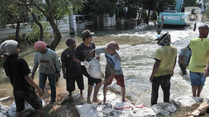 Pekerja menyelesaikan perbaikan tanggul jebol di Kompleks Perumahan Pantai Mutiara, Pluit, Jakarta, Minggu (7/6/2020). Tanggul jebol dengan panjang sekitar 10 meter yang terjadi bersamaan air pasang pada Sabtu (6/6) menyebabkan perumahan tersebut terendam banjir rob. (Liputan6.com/Iqbal S. Nugroho)