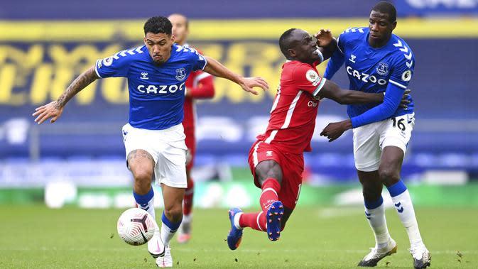 Pemain Everton Allan (kiri) dan Abdoulaye Doucoure (kanan) berebut bola dengan pemain Liverpool Sadio Mane pada pertandingan Liga Premier Inggris di Stadion Goodison Park, Liverpool, Inggris, Sabtu (17/10/2020). Pertandingan berakhir dengan skor 2-2. (Laurence Griffiths/Pool via AP)