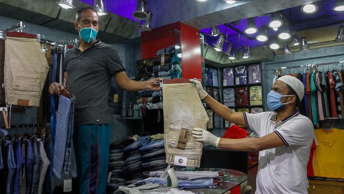 Seorang pria memilih celana di sebuah toko di pasar yang kembali dibuka, Dhaka, Bangladesh, Senin (11/5/2020). Jalan-jalan utama Dhaka kembali ramai sehari setelah toko-toko dan pasar kembali dibuka secara terbatas mengikuti aturan pemerintah. (Xinhua/Stringer)