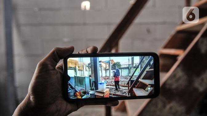 Wiwiek (56) menunjukkan foto sebelum akses menuju rumahnya ditutup tembok pembangunan sekolah Pergunas I di Jalan Cempaka Baru I, RT 015/003, Kemayoran, Jakarta, Senin (31/8/2020). Pembangunan itu menutup akses jalur keluar masuk dan harus melewati pintu samping. (merdeka.com/Iqbal S Nugroho)