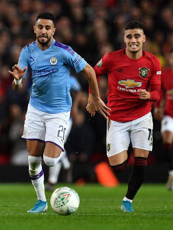 Gelandang Manchester United, Andreas Pereira dan gelandang Manchester City, Riyad Mahrez mengejar bola selama pertandingan leg pertama semifinal Piala Liga Inggris di Old Trafford (7/1/2020). City menang 3-1 atas MU. (AFP/Paul Ellis)