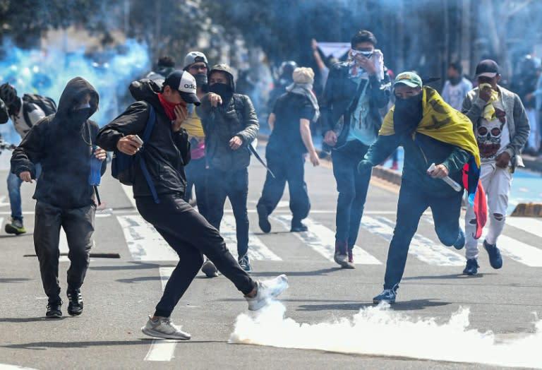 Demonstrators confront riot police during a protest in Bogota on November 23, 2019